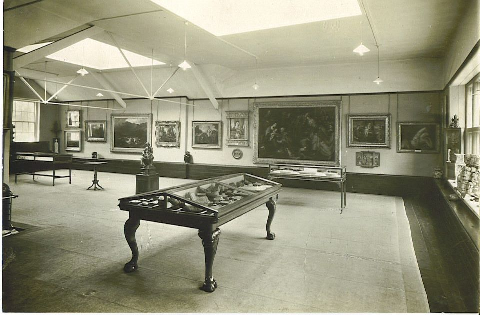 Gallery room with art on the walls and cases in the foreground displaying ceramics.