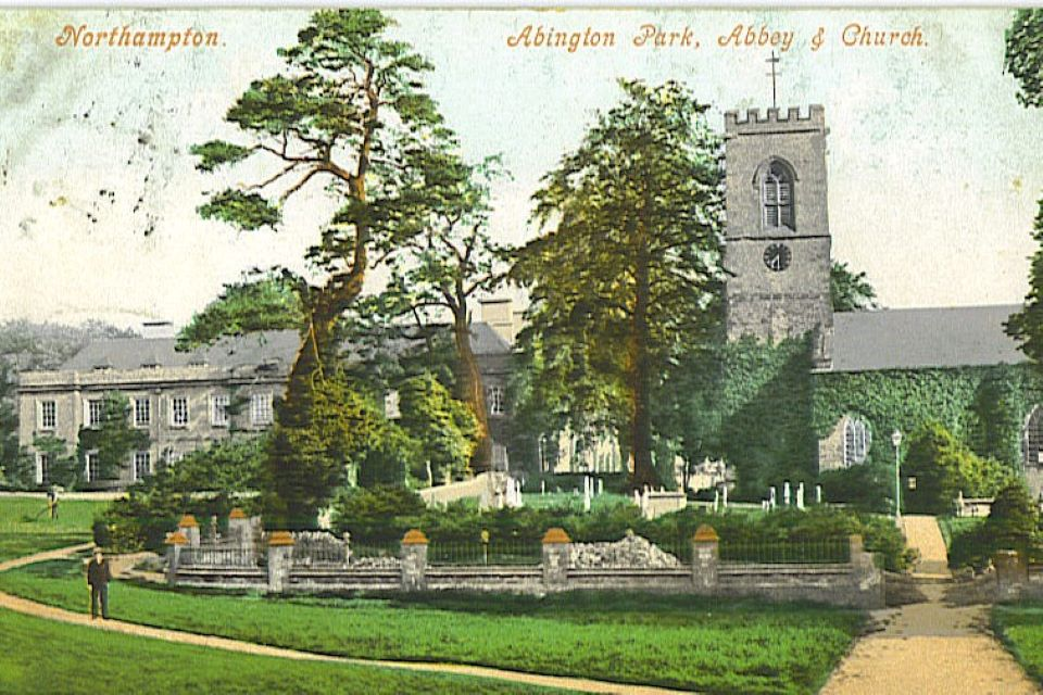 Postcard image of Abington Park Museum with tress and parkland in front of the building..