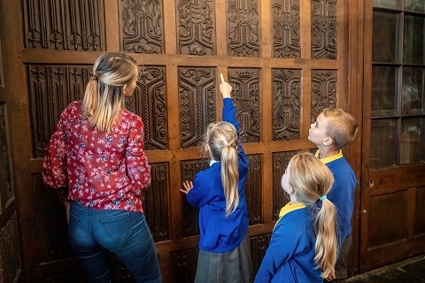 Teacher and three children looking at oak paneling.
