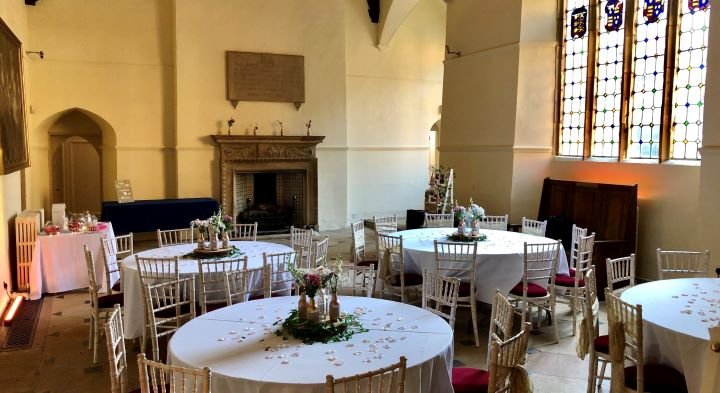 Image of the Great Hall with round tables and chairs set out for a wedding reception.