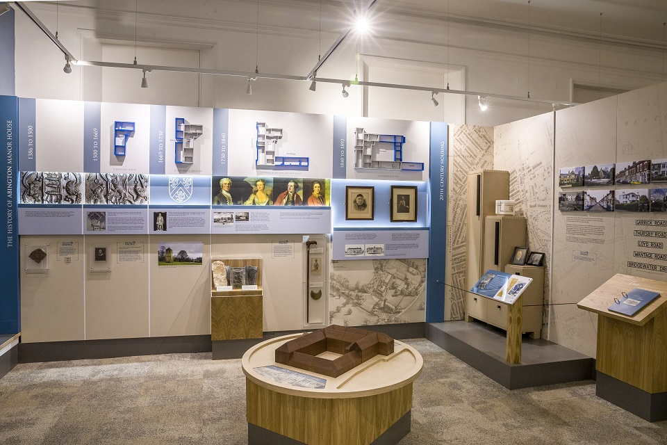 Gallery room with objects in cases and text panels on the walls. A central circular plinth with a wooden build a church interactive.