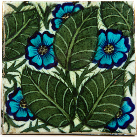 Earthenware Tile decoratived with a blue primrose design with green leaves designed by William De Morgan
