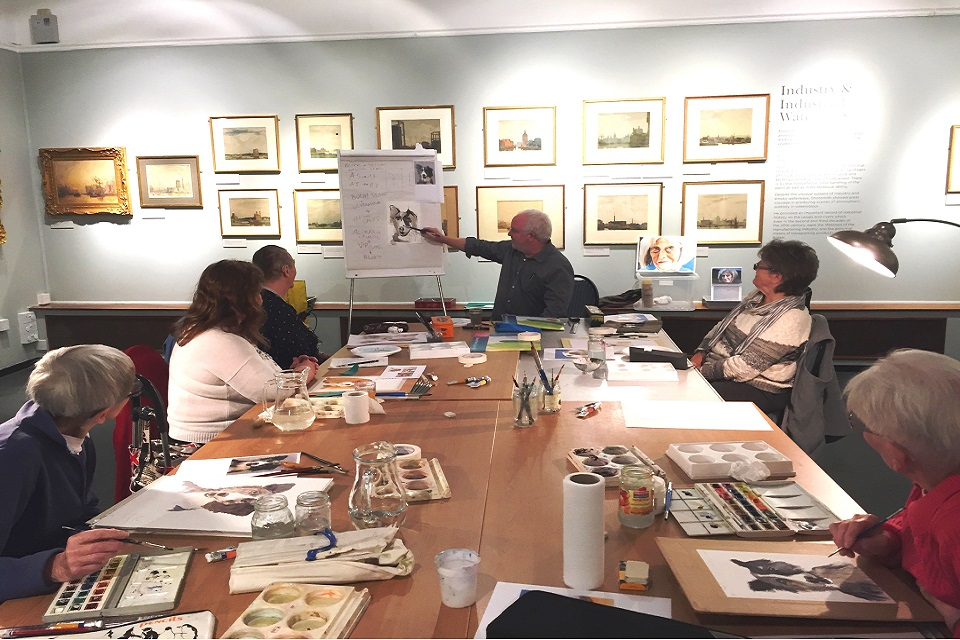 Group of adults with a tutor in a watercolour painting workshop.
