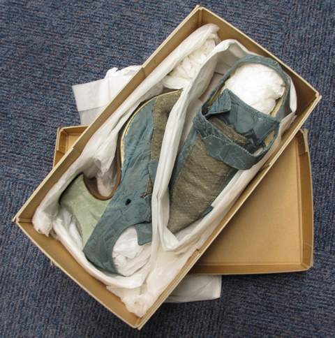 A card box packed with tissue holding two shoes.