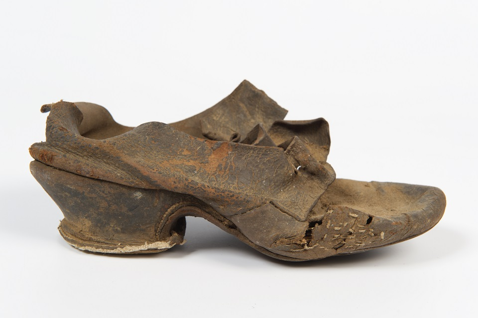 Women's black leather buckle latchet shoe, about 1750. It was found concealed in the flue above one of the ovens with a pair of shoes and a single shoe wrapped in a piece of brown paper, together with a leather gaiter and a wooden oven peel.