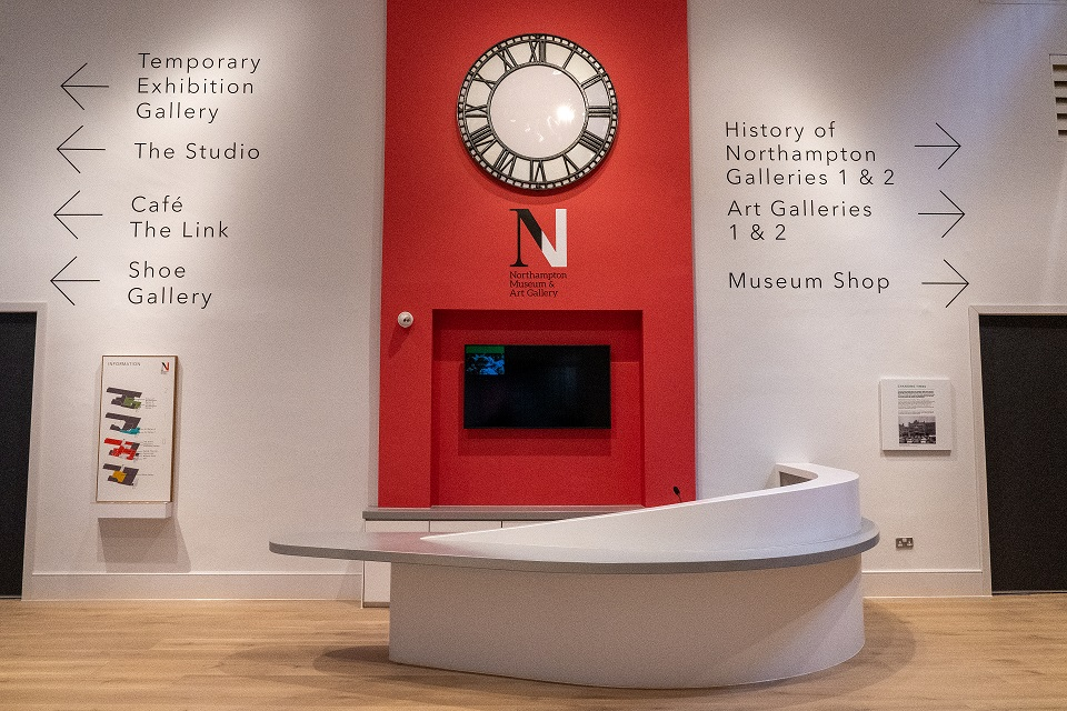 White desk with red wall behind displaying gallery directional signage and a clock.
