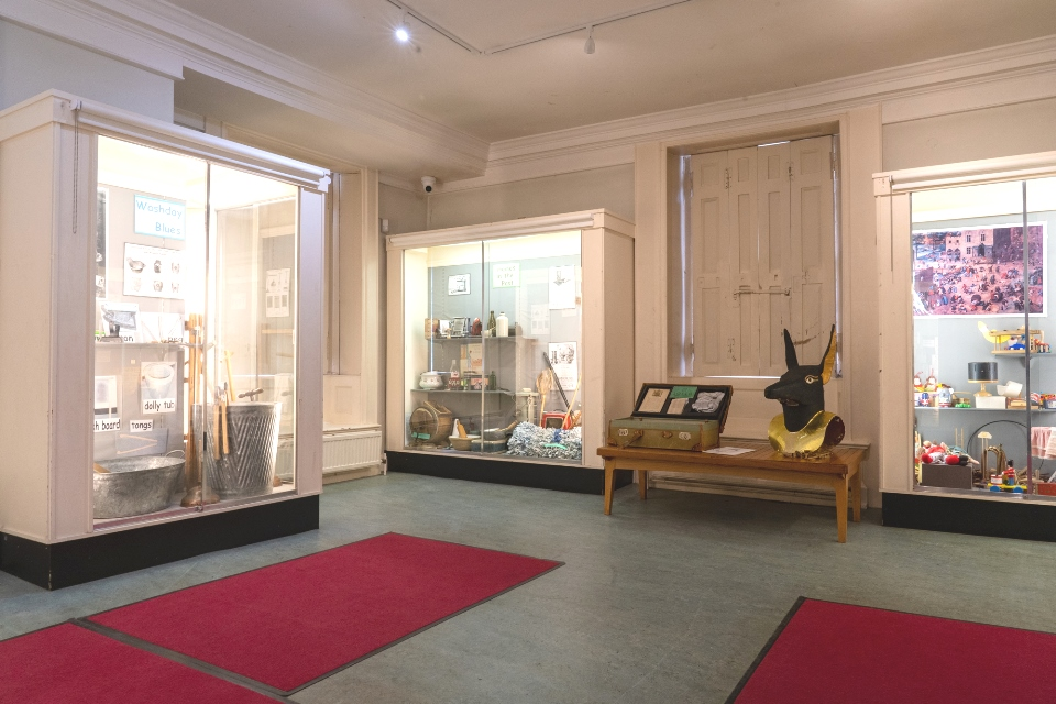 Room with two large glass display cases with museum objects. Two red mats on the foreground floor.