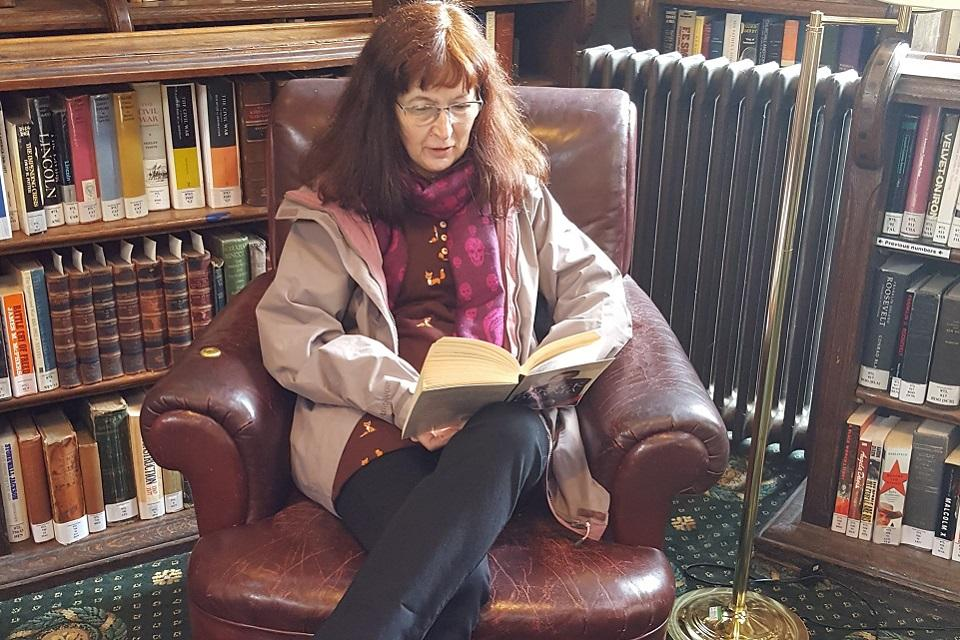Seated figure sitting in front of library shelves reading a book.