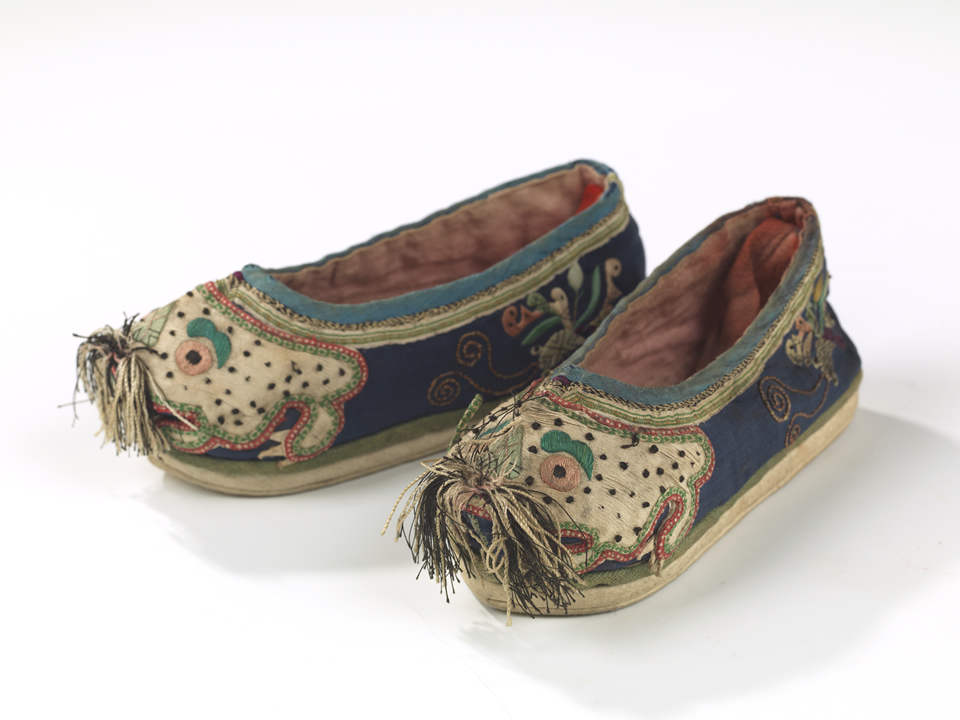 Two shoes angled towards the camera with tiger faces and fabric tassels.