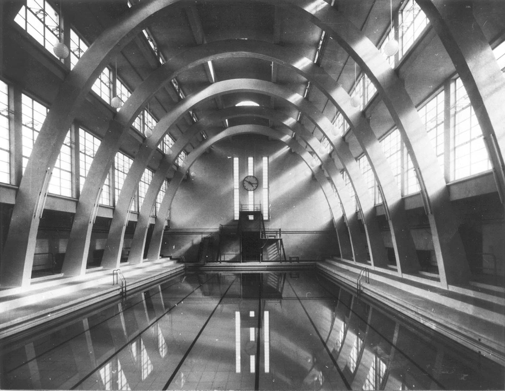 Black and white photograph depicting curved glazed roof with radial solid supports and water of pool at bottem.