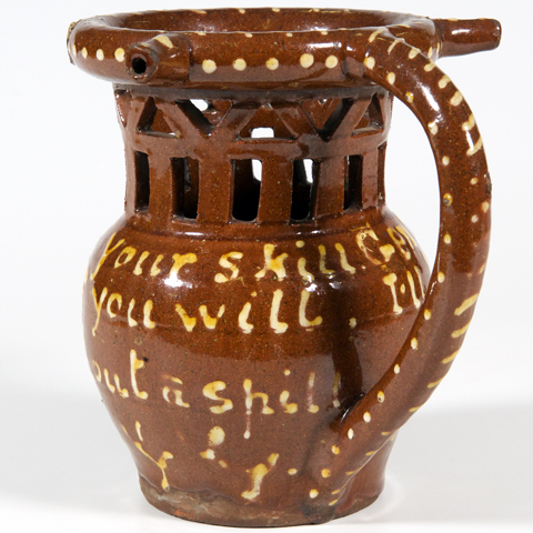 A brown puzzle jug decorated with writing and cut out holes