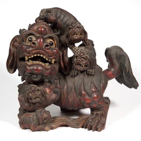 a wooden guardian lion figurine known as a foo dog